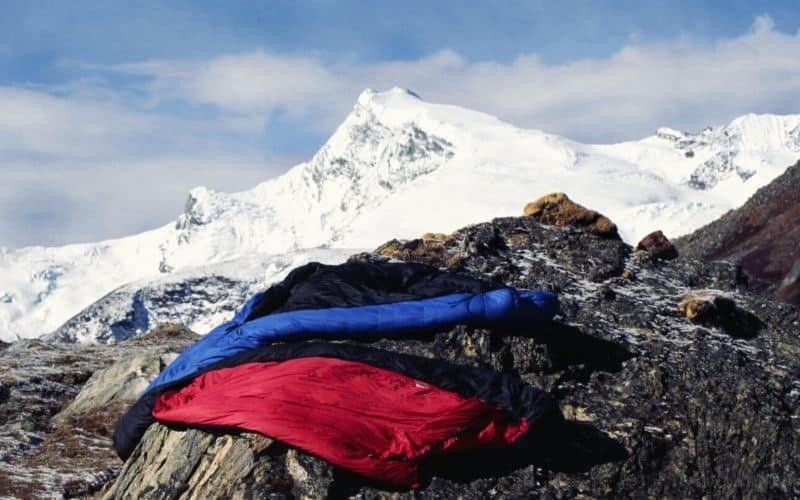 two sleeping bags on rock surface with snowy mountains in background