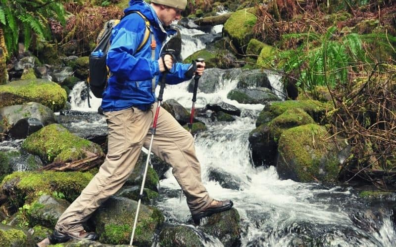 hiker crossing stream in hiking boots with trekking poles